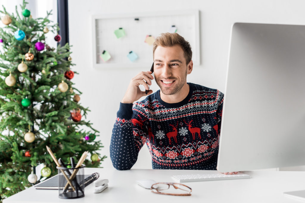 Man in holiday sweater working
